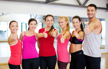athletic wear: fitness, sport, training, gym and lifestyle concept - group of happy people in the gym showing thumbs up Stock Photo