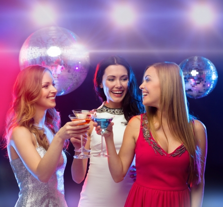 night out: new year, celebration, friends, bachelorette party, birthday concept - three women in evening dresses with cocktails and disco ball Stock Photo