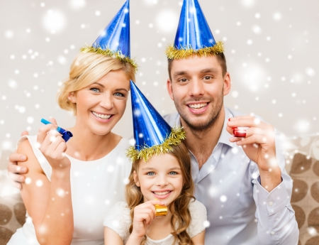celebration, family, holidays and birthday concept - three smiling women wearing blue hats and blowing favor horns photo