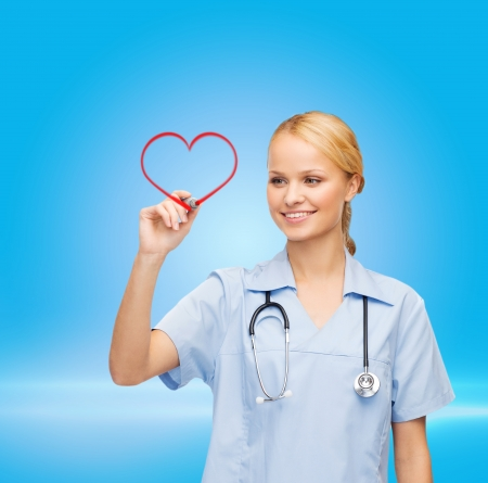 healthcare, medical and technology - young doctor or nurse drawing red heart photo