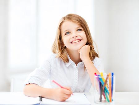 教育、作成および学校のコンセプト - ほとんどの学生少女を描くと学校で空想を笑顔