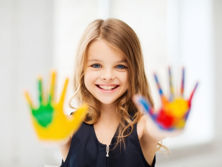 hand painting: education, school, art and painitng concept - smiling little student girl showing painted hands at school Stock Photo