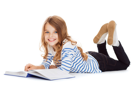 education and school concept - smiling little student girl with book lying on the floor Фото со стока