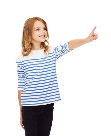 niño empujando: la educación, la escuela y el concepto de pantalla virtual - la niña linda que señala en el aire o la pantalla virtual