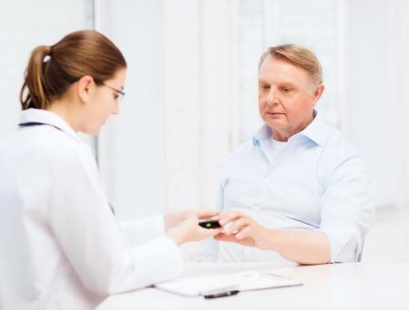 医療、高齢者と医療コンセプト - 女性医師や看護師測定患者の血糖値を持つ 写真素材