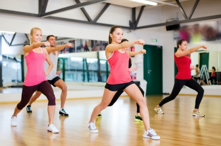 fitness, sport, training, gym and lifestyle concept - group of smiling people exercising in the gym