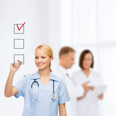 healthcare, medical and technology - smiling doctor or nurse drawing red checmark into checkbox photo