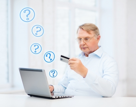 business, online banking, internet shopping and oldness concept - smiling old man with laptop computer and credit card at home photo