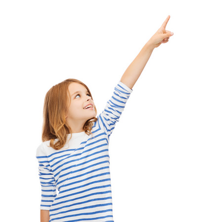 education, school and virtual screen concept - cute little girl pointing in the air or virtual screen photo