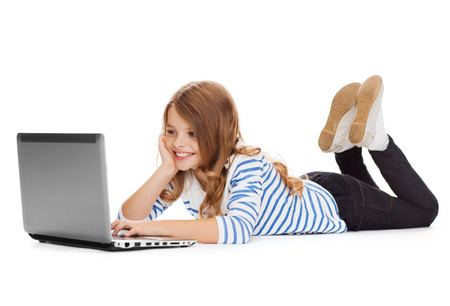 education technology: education, technology and internet concept - smiling little student girl with laptop computer lying on the floor