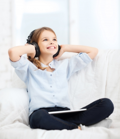child singing: home, leisure, new technology and music concept - smiling little girl with tablet pc computer and headphones at home