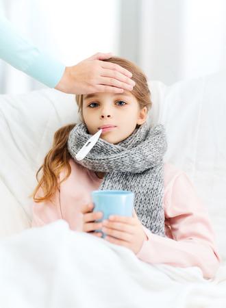 gezondheidszorg en de geneeskunde concept - ziek meisje kind met thermometer in de mond, een kop warme thee en zorgzame moeder