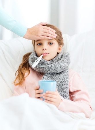 sick child: healthcare and medicine concept - ill girl child with thermometer in mouth, cup of hot tea and caring mother Stock Photo