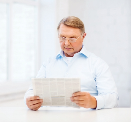 oldness, news, leisure and happiness concept - old man at home reading newspaper photo