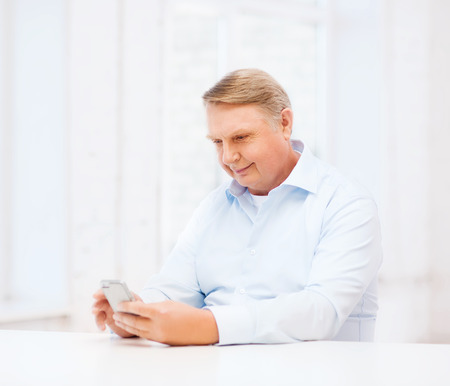 adult texting: oldness, new technology, office and happiness concept - old man at home with smartphone