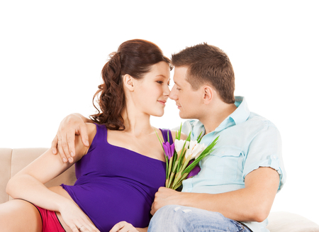 love, relationship, anniversary concept - happy expecting parents with flowers at home Stock Photo - 24117240