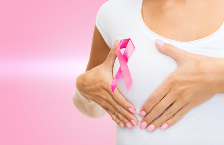cancer ribbon: healthcare and medicine concept - woman in blank t-shirt with pink breast cancer awareness ribbon checking breast