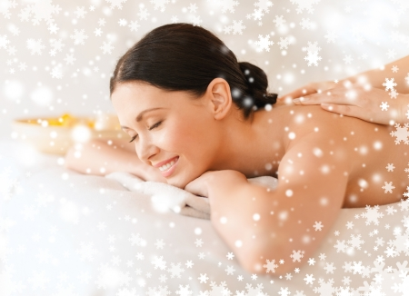therapeutic massage: health and beauty, resort and relaxation concept - woman in spa salon getting massage Stock Photo
