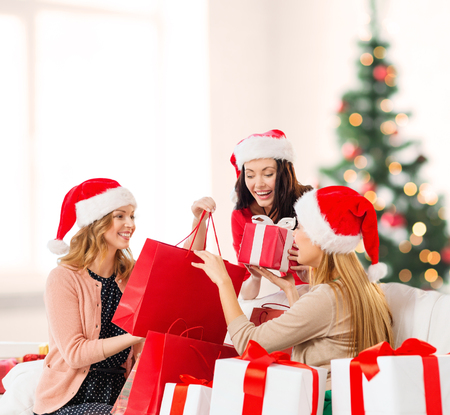 christmas shopper: shopping, sale, gifts, christmas, x-mas concept - smiling women in santa helper hats with shopping bags and many gift boxes