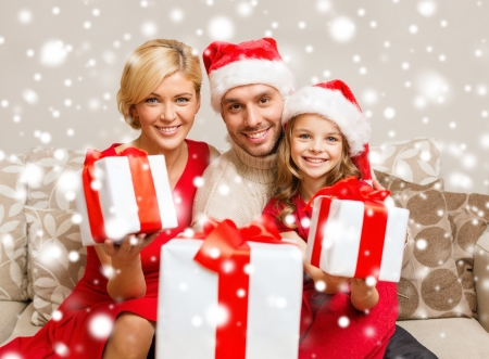 multiple family: family, christmas, x-mas, winter, happiness and people concept - smiling family in santa helper hats with many gift boxes Stock Photo