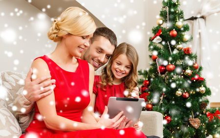 family, christmas, x-mas, winter, happiness, technology and people concept - smiling family with tablet pc photo