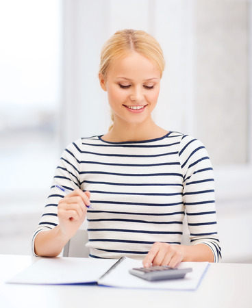 education, school and business concept - smiling woman with notebook and calculator studying in college