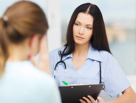 medicine and health concept - female doctor or nurse with concerned patient photo