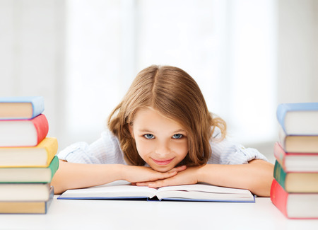 wondered: education and school concept - smiling little student girl with many books at school Stock Photo