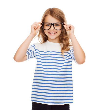 cute little girl smiling: education, school and vision concept - smiling cute little girl with black eyeglasses