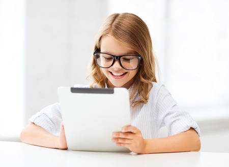 education, school, technology and internet concept - little student girl in black eyeglasses with tablet pc computer at school photo