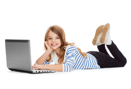 new technology: education, technology and internet concept - smiling little student girl with laptop computer lying on the floor