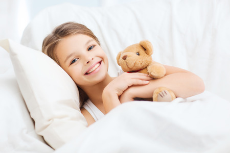 pillow: health and beauty concept - little girl with teddy bear sleeping at home