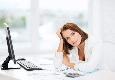 social work: business, education and technology concept - stressed businesswoman with computer, papers and calculator in office