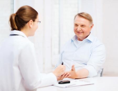 gezondheidszorg, ouderen en medische concept - vrouwelijke arts of verpleegkundige met de patiënt meten bloedsuikerwaarde