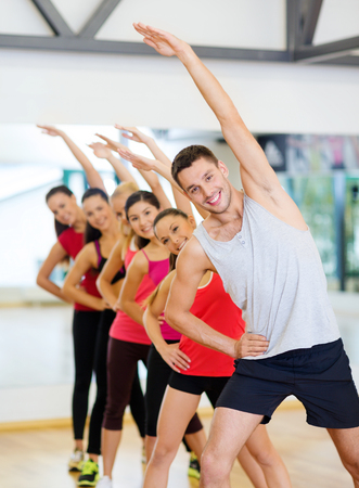 fitness, sport, training, gym and lifestyle concept - group of smiling people stretching in the gym Stock Photo - 24117710
