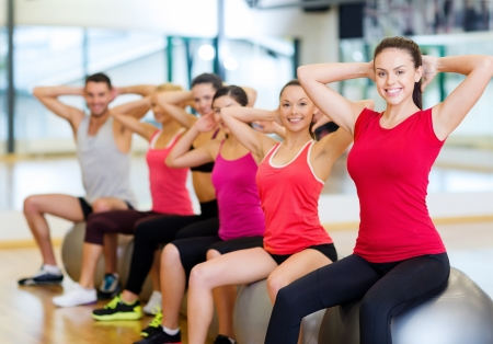 fitness, sport, training, gym and lifestyle concept - group of smiling people working out in pilates class photo