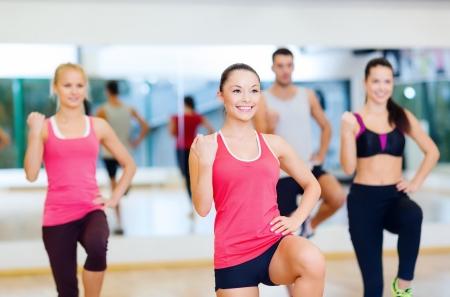 třída: fitness, sport, trénink, posilovna a koncept životního stylu - skupina lidí, usměvavá s trenérem cvičení v posilovně