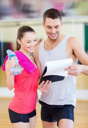 figure out: fitness, sport, training, gym and lifestyle concept - smiling male trainer with clipboard and woman with water bottle in the gym