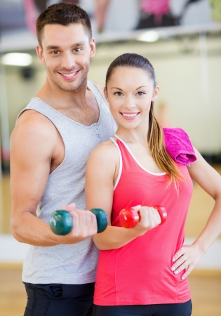 couple exercising: fitness, sport, training, gym and lifestyle concept - two smiling people working out with dumbbells in the gym