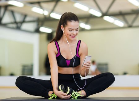 exercising: fitness, sport, training, gym, technology and lifestyle concept - smiling woman with smartphone Stock Photo