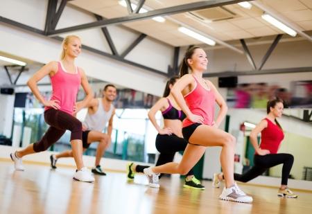 fitness hombres: fitness, deporte, entrenamiento, gimnasio y estilo de vida concepto - grupo de gente sonriente que ejercita en el gimnasio
