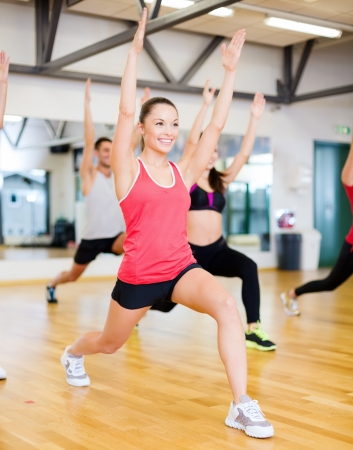 weight training: fitness, sport, training, gym and lifestyle concept - group of smiling people exercising in the gym