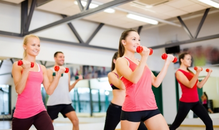 gym class: fitness, sport, training, gym and lifestyle concept - group of smiling people working out with dumbbells in the gym