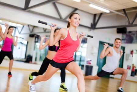 uygunluk: spor, spor, eğitim, spor ve yaşam tarzı konsepti - spor salonunda barbell ile çalışma dışarı gülümseyen insanlar grubu