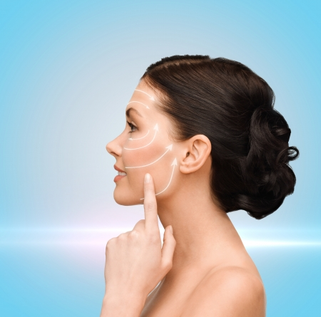 cosmetic surgery: beauty, spa and health concept - smiling young woman pointing to her cheek