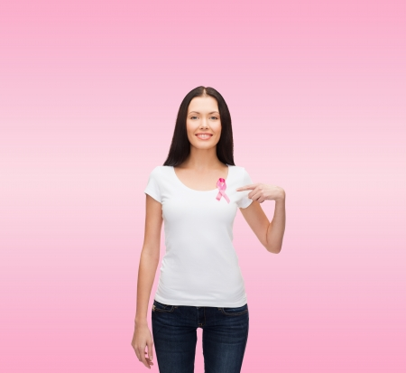 healthcare and medicine concept - smiling woman in blank t-shirt with pink breast cancer awareness ribbon photo