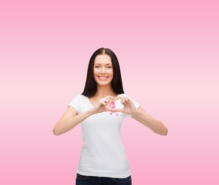 healthcare and medicine concept - smiling woman in blank white t-shirt with pink breast cancer awareness ribbon showing heart shape photo