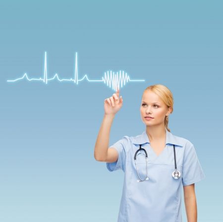healthcare, medicine and technology concept - smiling young doctor or nurse pointing to cardiogram photo