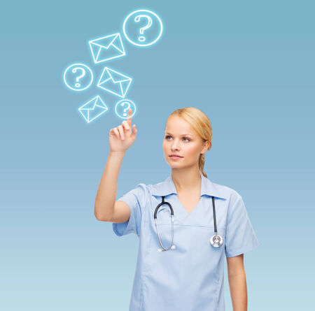healthcare, medicine and technology concept - smiling young doctor or nurse pointing to something or pressing imaginary button photo