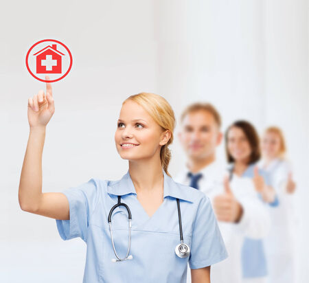 healthcare, medicine and technology concept - smiling young doctor or nurse pointing to red hospital icon photo